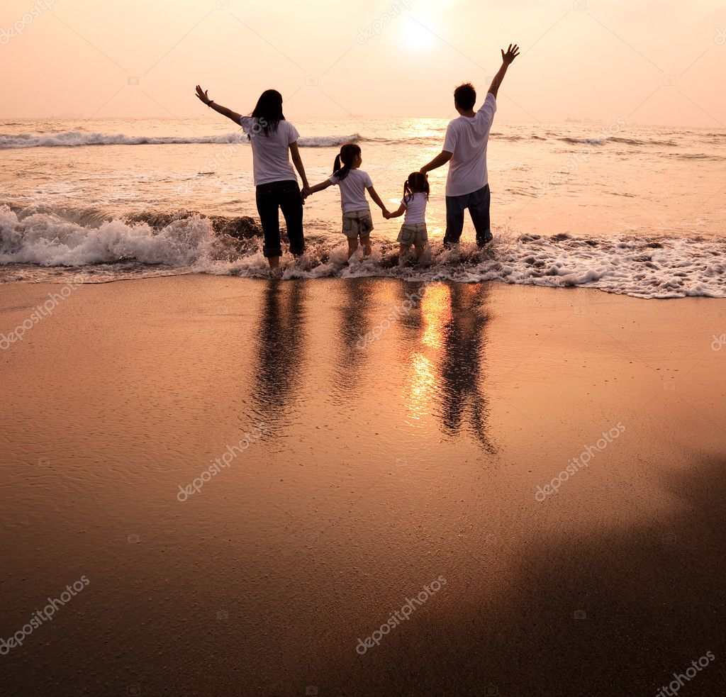 Happy family holding hands on beach and watching the sunset