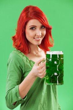 Redhead drinking green beer