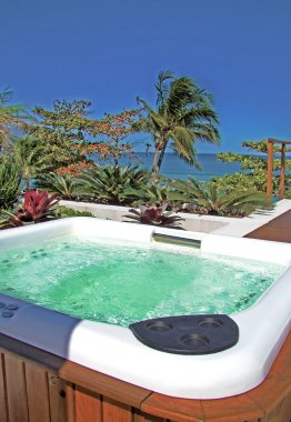 Modern spa jacuzzi outdoors under beautiful blue sky