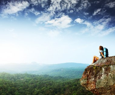 Young woman with backpack sitting on cliff and looking to a sky stock vector