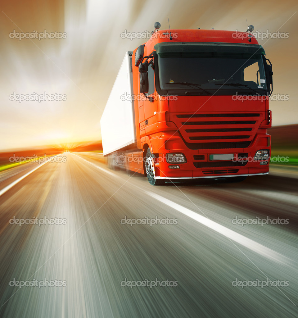 Red truck on blurry asphalt road and motion blured sky