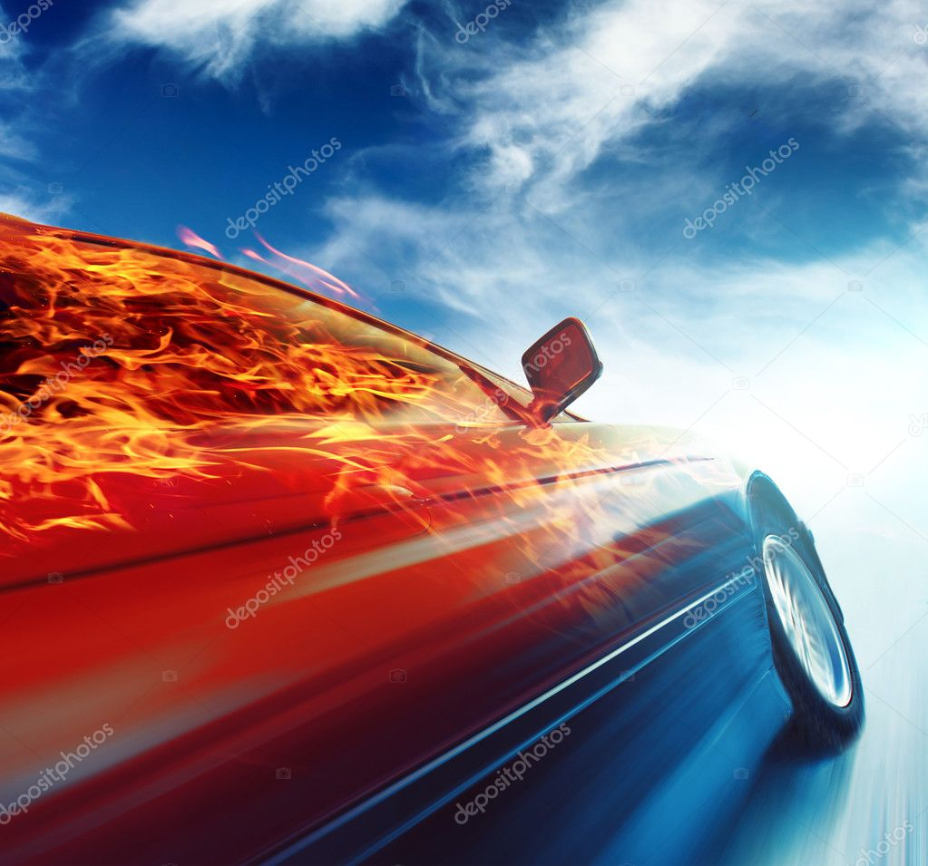 Burning car in motion over blue sky background