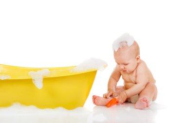 Baby sits beside bath