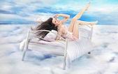 bruneta krása ležící na posteli v mracích