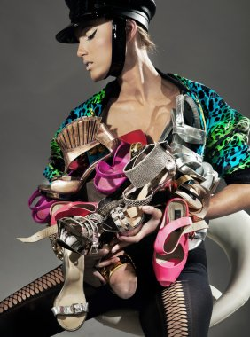 Sexy lady holding many pairs of shoes