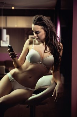 Sexy young lady writing a text message