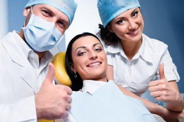 Dentist with assistant and smiling patient showing thumb up