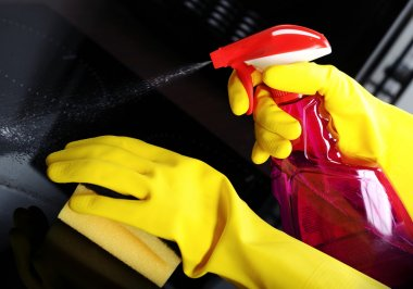 Woman with sponge and rubber gloves cleaning kitchen