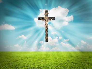 Jesus Christ on cross radiates light in sky over landscape