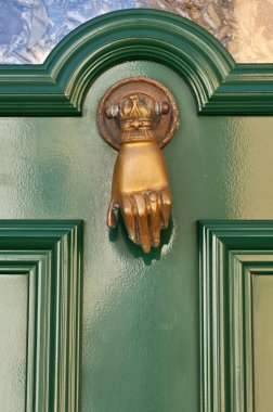 Old knocker in the shape of a hand on a door