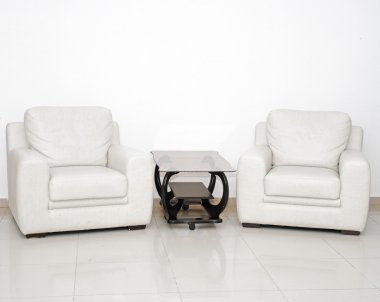 Detail of a modern living room with white armchair and glass cof