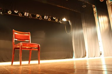 Red chair on empty stage lighted with spotlights stock vector