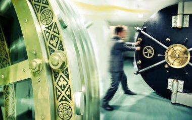 Banker is opening safe door