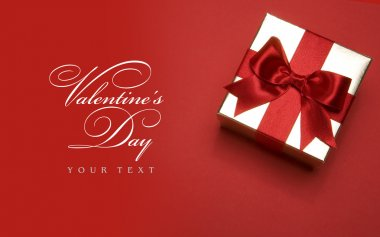 Art Valentines day golden gift box with a red bow on red background
