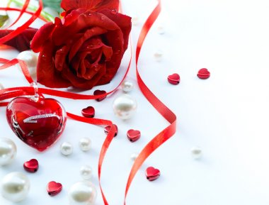 Valentines greeting card with red roses petals and jewelry hear