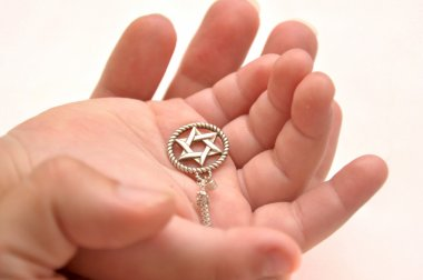 Mother and child's hands holding silver star of David stock vector