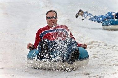 Man Tubing in Snow