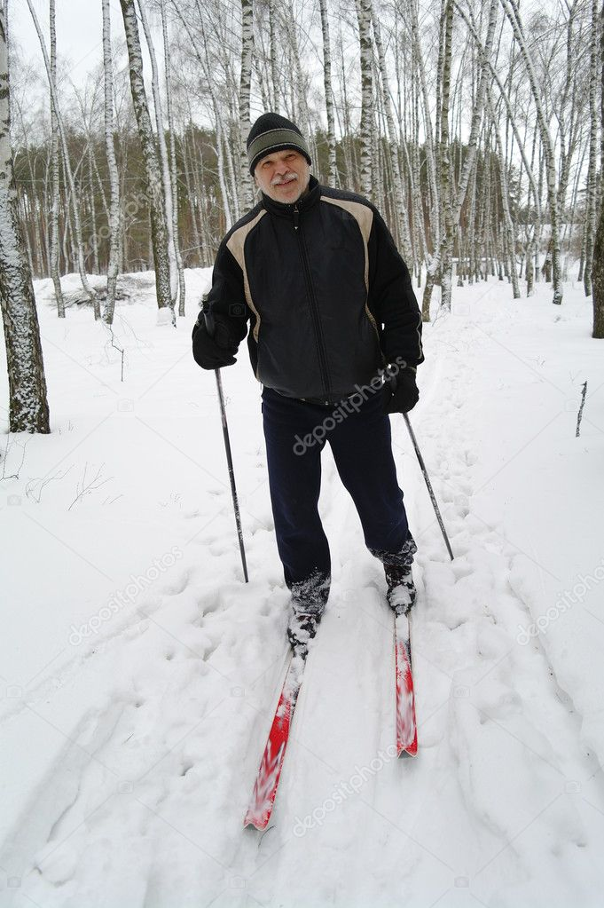 An elderly man stands on the cross-country skiing in the park in winter