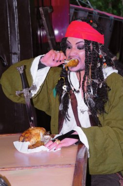 Actor Jack Sparrow in the form of eating chicken grilled on a sailing ship