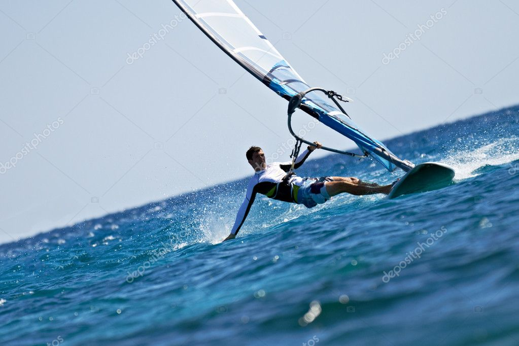 Young man surfing the wind in splashes of water