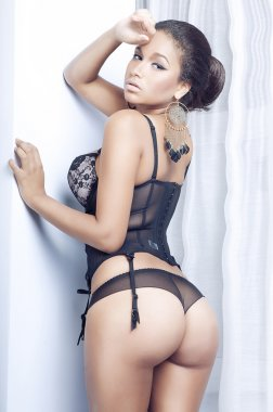 Sexy african woman posing in lingerie showing ideal buttocks