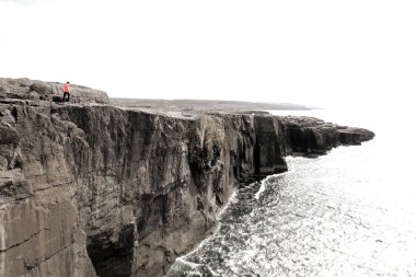 Lone person on cliffs edge