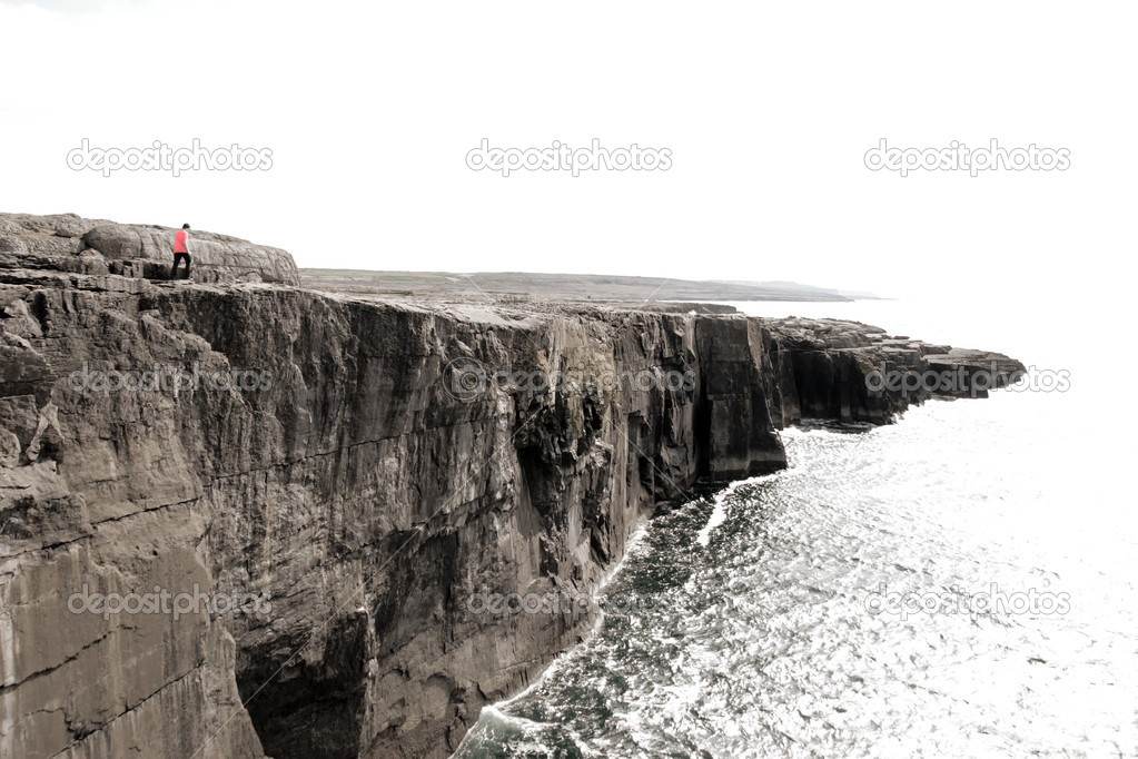 Lone person on cliffs edge