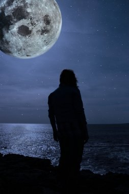Silhouette of a sad lone woman with a full moon on a cliff edge
