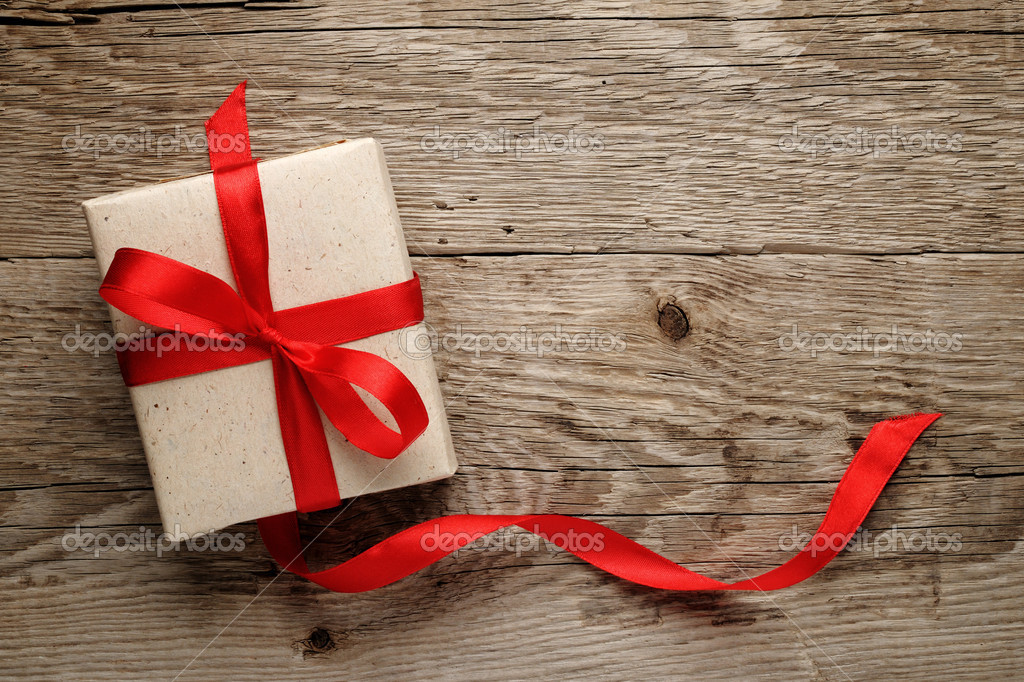 Gift box with red bow on wood background