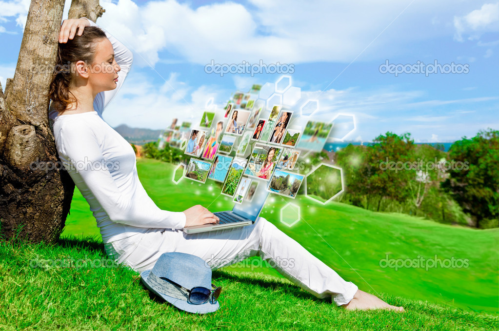 Pretty woman sitting by tree with laptop computer