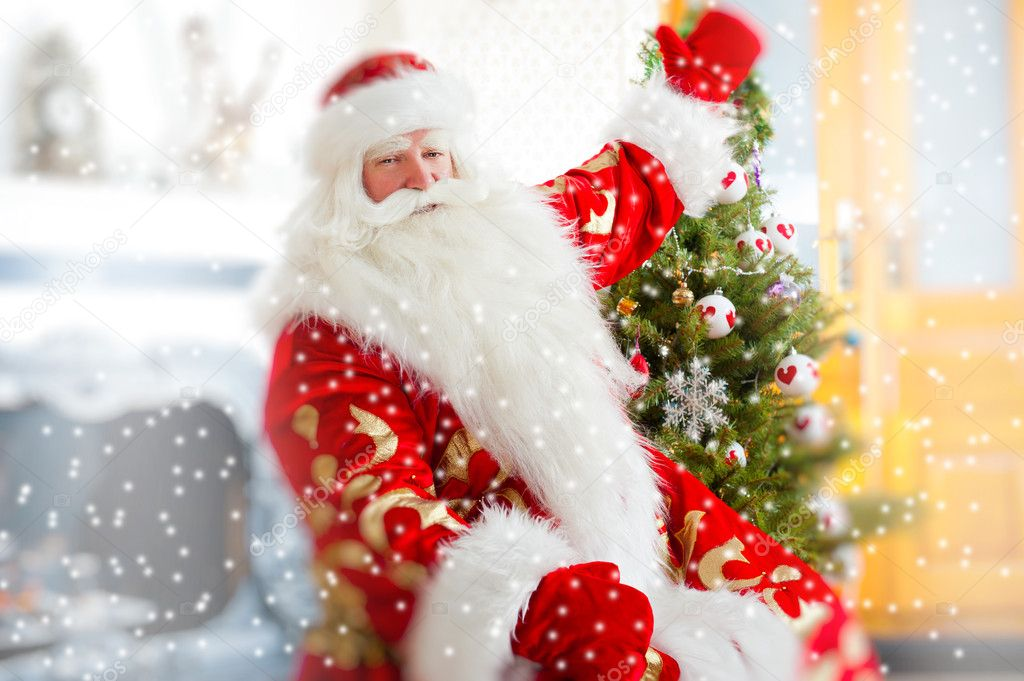 Santa sitting at the Christmas tree, near fireplace and looking at camera. Indoors. Magic snowy poster