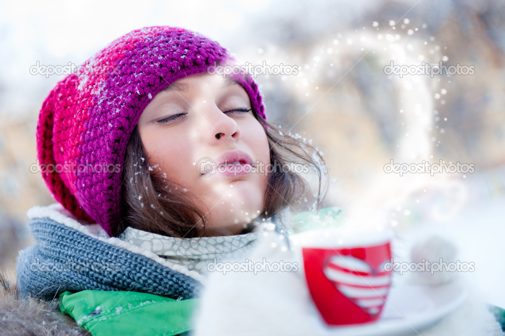 Young beautiful girl dreaming of love outdoors in winter while h