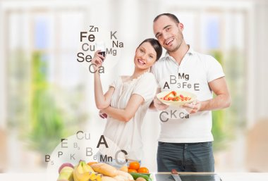 Playful young couple in their kitchen preparing healthy food and