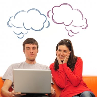 Smiling beautiful couple sitting on a sofa using laptop and drea