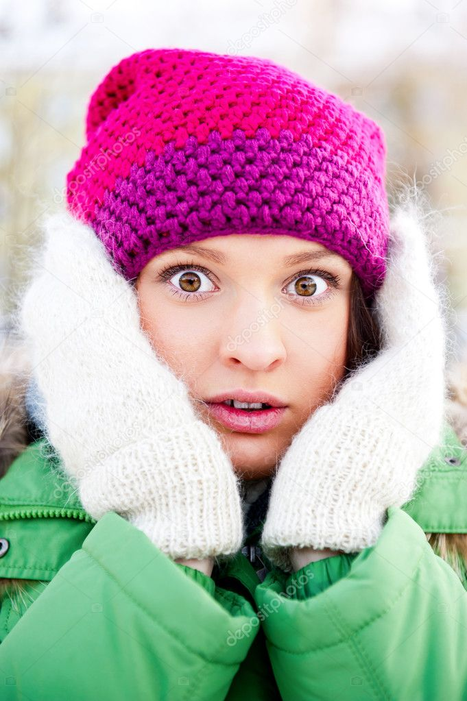 Portrait of a shocked woman in winter park looking at camera