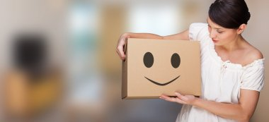 Attractive woman with box making a removal. Smile face illustrated on box. Easy, happy carefree moving concept