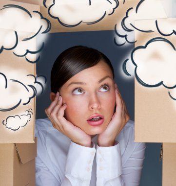 Portrait of young woman surrounded by lots of boxes. Lots of work concept. Help needed. Blank cloud balloons overhead