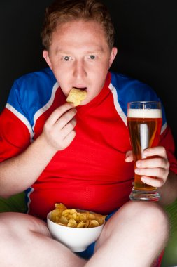 Close-up portrait of young man wearing sportswear fan of football team is watching tv and rooting for his favorite team. Sitting on beanbag alone at night drinking beer and eating chips