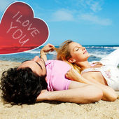 Young beautiful romantic couple relaxing on beach at sunny day. Heart and sign i love you