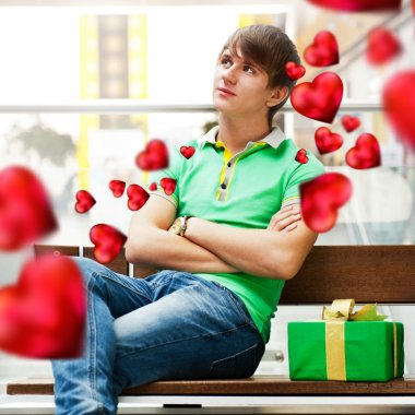 Portrait of young man inside shopping mall with gift box waiting for his girlfriend. Valentine day. Red hearts flying around