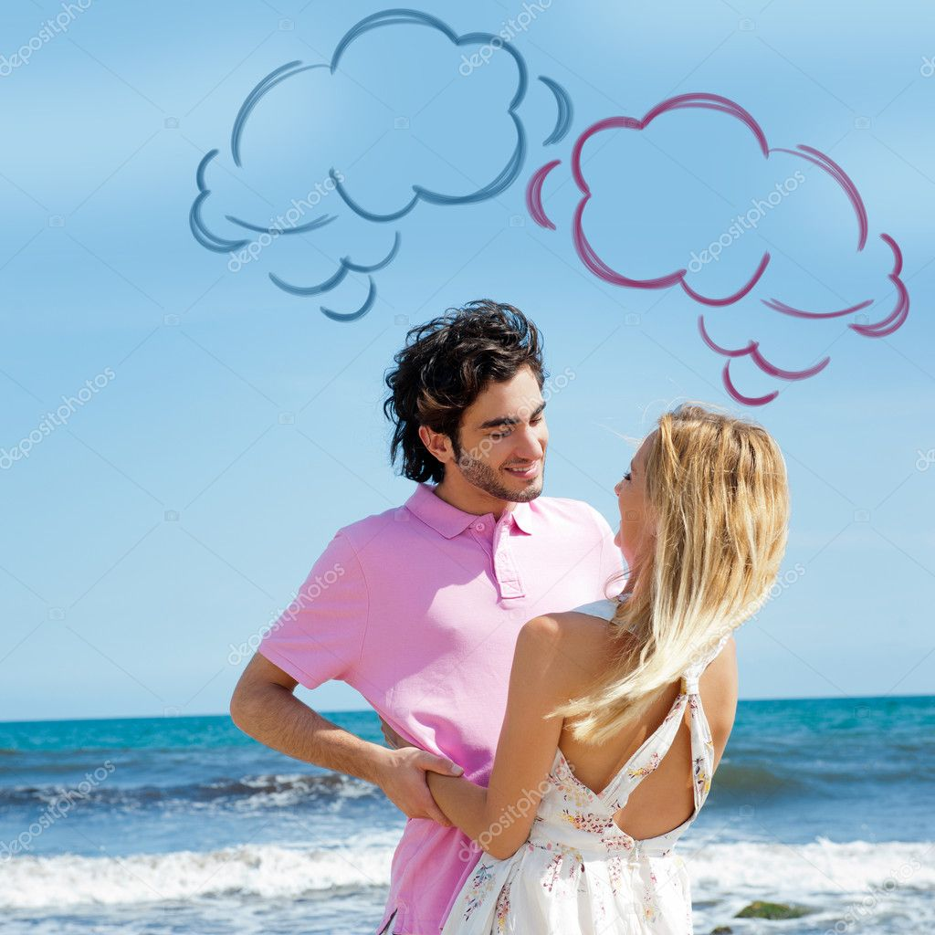 Young couple at beach, embracing, side view. Natural emotions. Happy life. Blank cloud balloons for their thoughts overhead