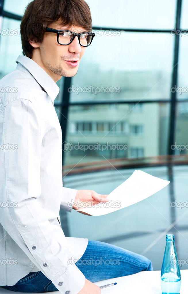 Close-up portrait of young creative businessman looking at camera while sitting relaxed on table at his office and holding papers