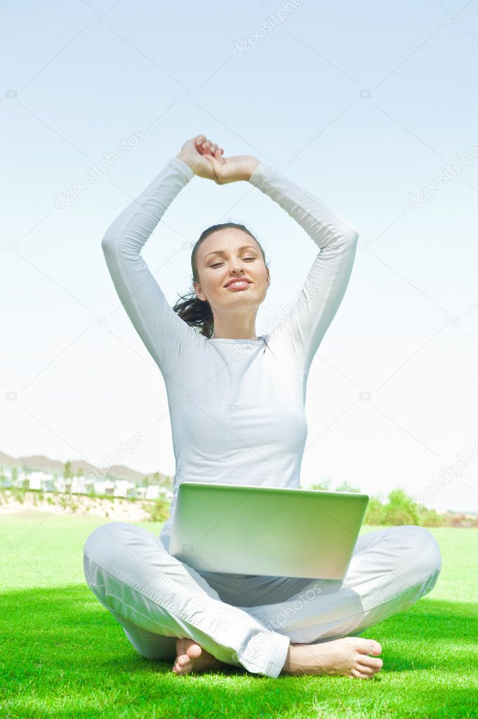 Pretty relaxed woman sitting on grass and stretching her arms aim to the sky while working on her laptop