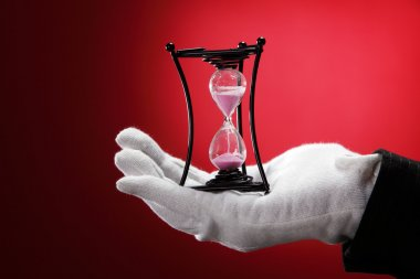 Man with the white hand glove holding an hour glass