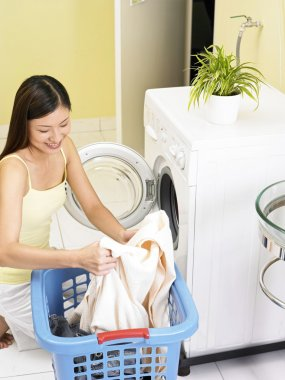 Woman in front of the washing machine