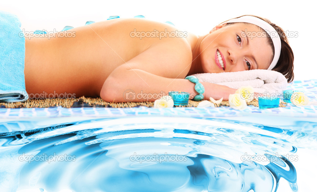 A picture of a young beautiful woman having stone massage in exotic spa centre