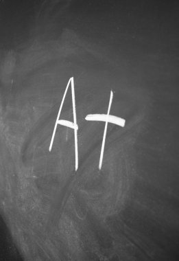 A+ sign written with chalk on blackboard