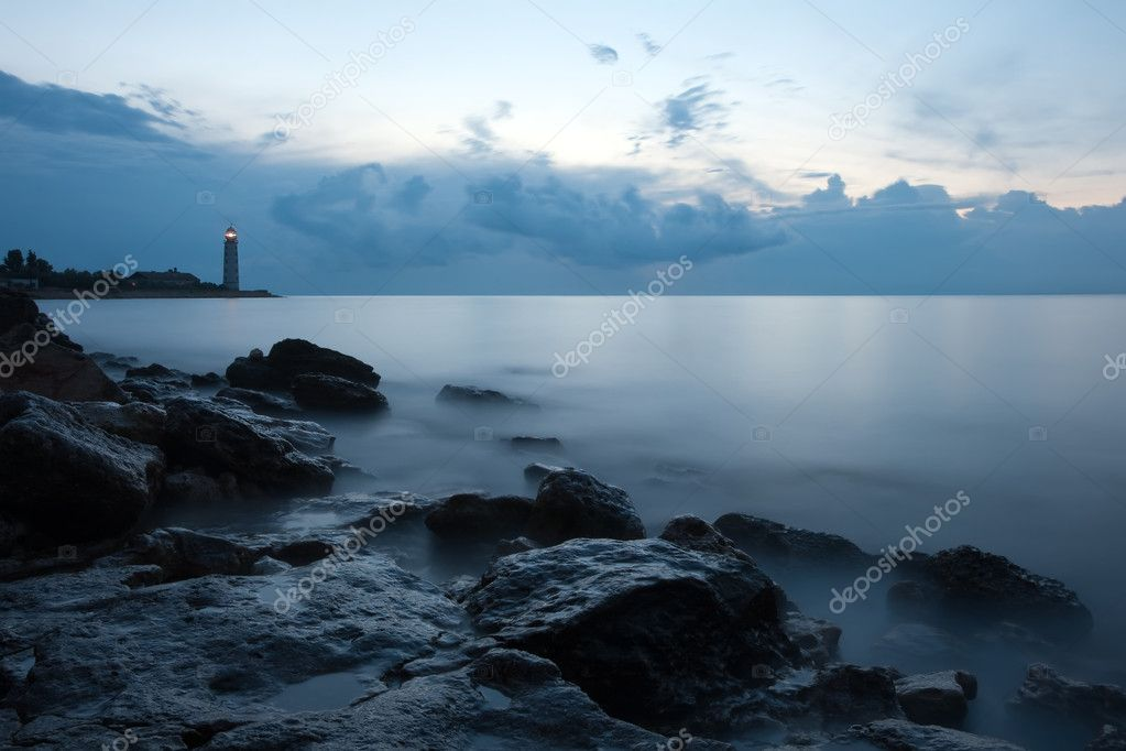 Nightly seascape with lighthouse and moody sky