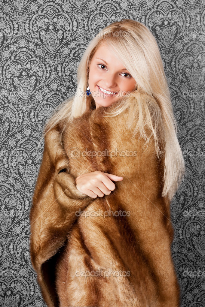 Attractive blond girl in a fur coat