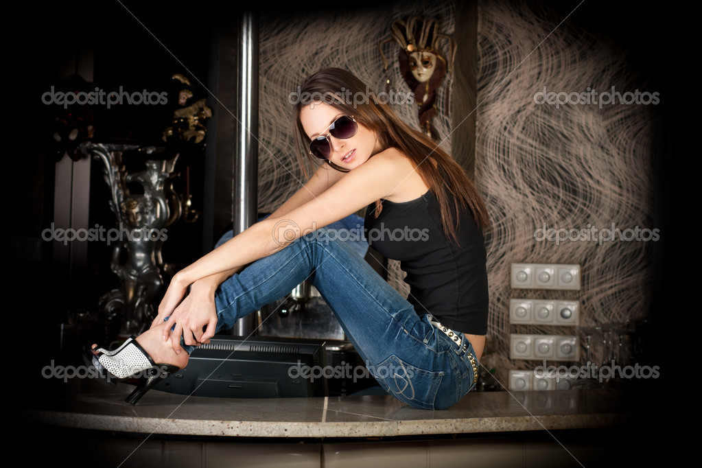 Hot and stylish brunette in sun glasses on a bar table